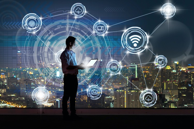 Image source: Talent & Organization Blog for Financial Services Asian businessman standing and using the laptop showing Wireless communication connecting of smart city Internet of Things Technology over the cityscape background, technology and innovation concept