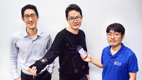 The smartphone-powered suit – pictured here with a design which resembles the motif on Spider-Man's suit – is designed by a team led by Asst Prof John Ho (left). With him are two members of the research team: Dr Lin Rongzhou (centre) and Dr Kim Han-Joon (right)